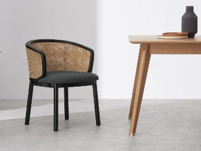 """Ein Stuhl vom Typ """"Panos"""" neben einem Tisch"""