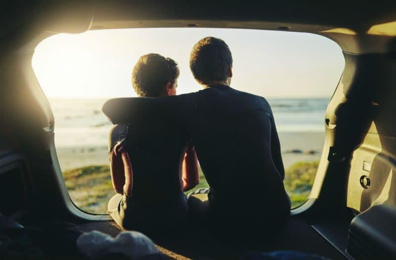 Glückliches Paar im Auto am Strand