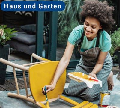 Frau sitzt im Garten und streicht einen Stuhl