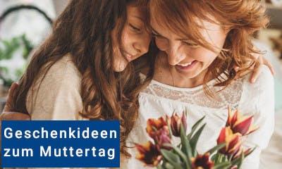 Mutter und Tochter stecken die Köpfe zusammen, unten im Bild ein Blumenstrauß
