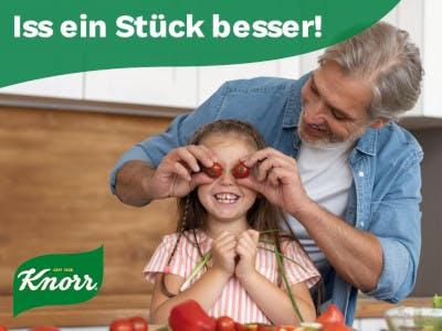 Vater und Tochter in der Küche, er hält ihr Tomaten vor die Augen