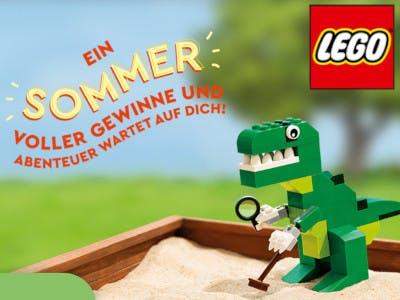 LEGO-Drachen spielt im Sandkasten, LEGO-Logo rechts oben, links im Bild der Gewinnspiel-Slogan