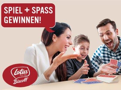 Frau, Mann und Kind beim Kartenspielen, oben links Aktions-Slogan, unten links das Lotus.Biscoff Logo