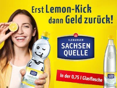Gelber Bildhintergrund, unten rechts eine 0,75l-Flasche , links daneben ein entsprechende roter Balken, links im Bild Frau mit Flasche in der Hand, die sich mit einer Zitronenscheibe das rechte Auge zuhält. Mittig das Sachsen Quelle Logo