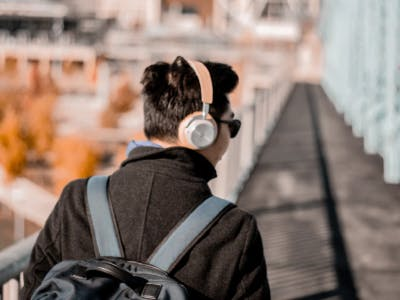 Mann läuft auf einer Brücke und hört Musik