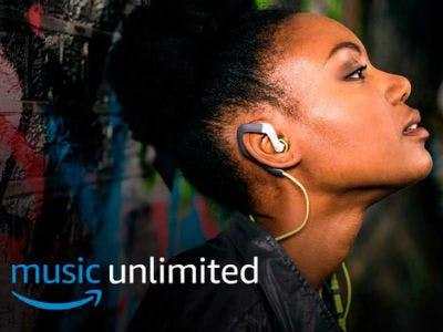 Eine dunkelhäutige Frau hat Kopfhörer im Ohr und genießt es ihre Musik zu hören
