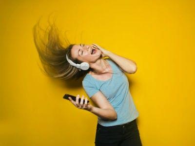 junge Frau hat Kopfhörer auf und tanzt zur Musik