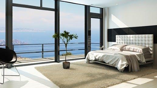 Ein Hotelzimmer von innen. Draußen sieht man Meer und Palmen.