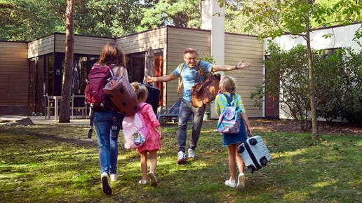 Eine Familie kommt an ihrem Ferienhaus an und freut sich.