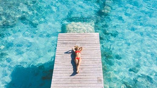 Eine Frau liegt auf einem Steg, der ins Meer führt.