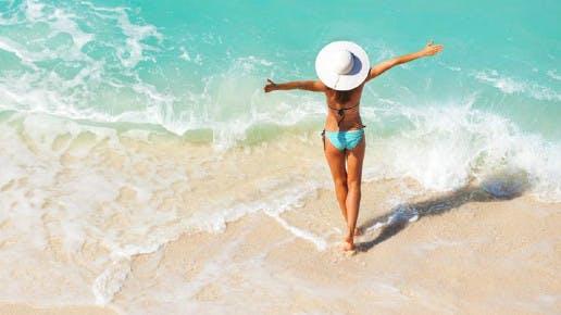 Eine Frau steht mit offenen Armen am Strand.
