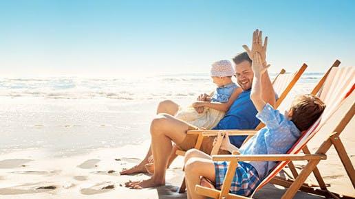 Ein Vater mit 2 Kindern am Strand. Sie sitzen in Sonnenstühlen.