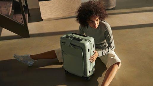 Eine Frau sitzt vor einem Koffer.