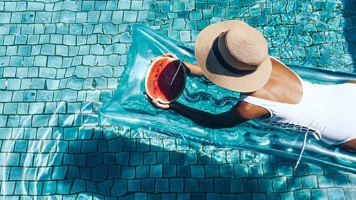 Eine Frau liegt auf einer Luftmatratze im Pool und hat eine Melone in der Hand.