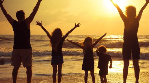 Eine Familie steht am Strand und reißt die Arme hoch.
