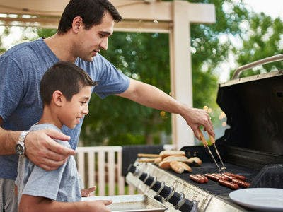 Ein Vater grillt mit seinem Sohn an einem Gasgrill