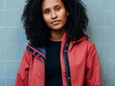 Eine junge hübsche Frau steht mit einer roten Regenjacke an eine Wand gelehnt