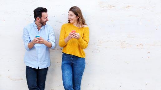 Ein Mann und eine Frau haben ein Handy in der Hand und gucken sich freudestrahlend an