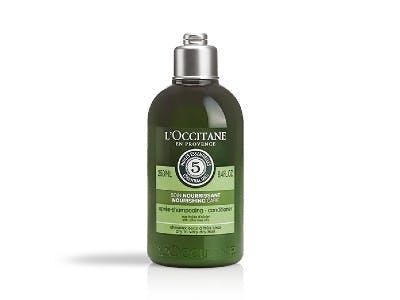 Grüne Haarspülung-Flasche auf weißem Hintergrund.