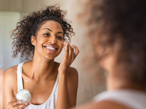 Eine junge Frau guckt in einem Spiegel und cremt sich ihr Gesicht ein.