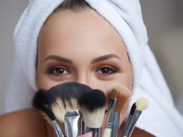 Eine Frau mit geschminkten Augen hält sich Make-up-Pinsel vors Gesicht.