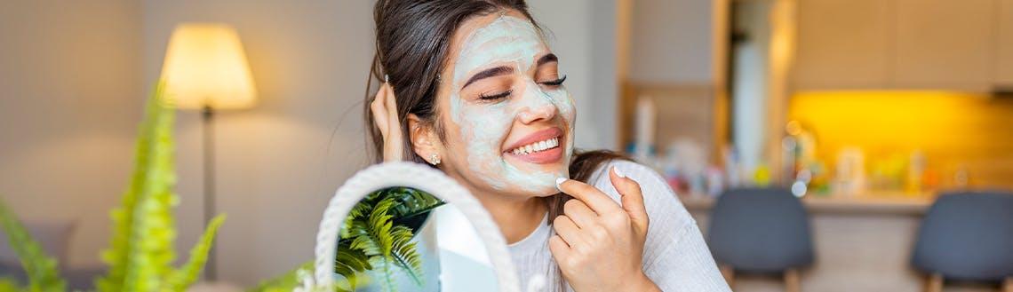 Eine Frau sitzt vorm Spiegel und trägt eine Gesichtsmaske auf.
