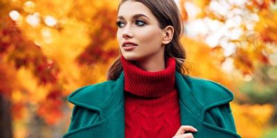 Herbstmode-Trends: Eine Frau mit Rollkragen-Pullover steht vor Bäumen mit bunten Blättern.