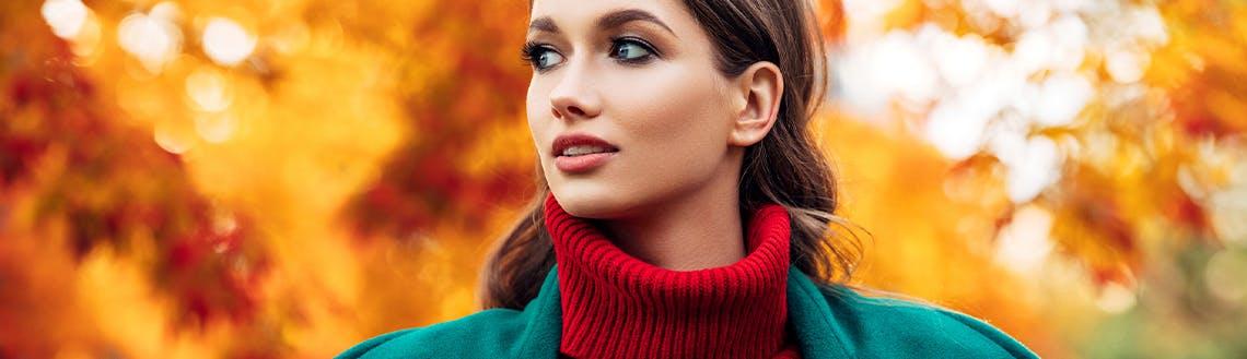 Herbstmode-Trends: Eine junge Frau steht vor bunten Blättern.