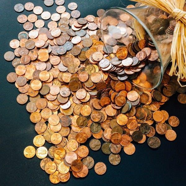 Geldmünzen, die auf einem Tisch verteilt sind.