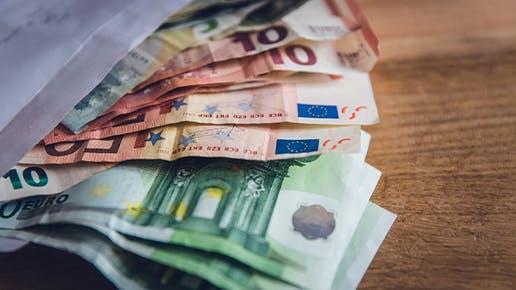 EIn Umschlag mit Geld, der auf einem Tisch liegt