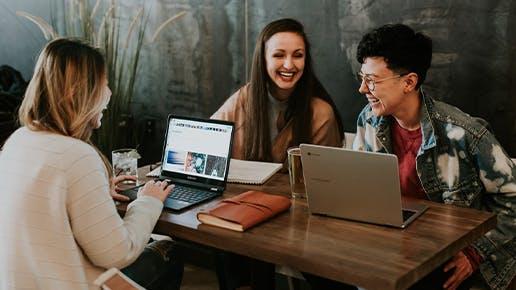 Drei Stundentinnen, die an ein einem Tisch mit Computern sitzen und lachen