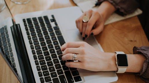 Frauenhände an einem Laptop