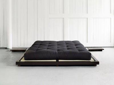 Ein schwarzes Futon-Bett mit schwarzer Matratze in einen leeren Raum