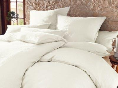 Ein Bett mit Kissen und Decken in Natur-Farbe vor einer rosa Wand