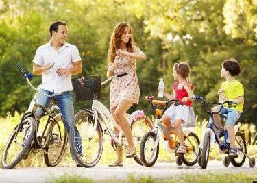 Eine Familie macht eine Fahrradtour an einem sonnigen Tag.
