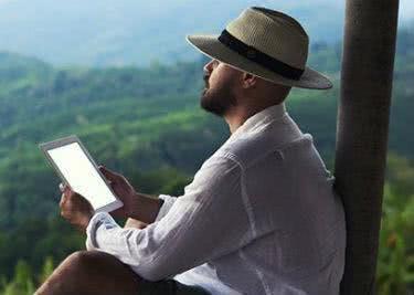 Ein Mann im Wald liest auf seinem Tablet, während er sich an einen Holzstamm lehnt.